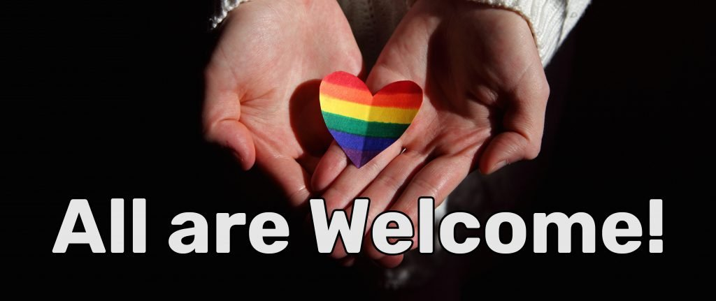 LGBT+ pride heart in outstretched hands. All are welcome!